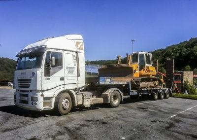 Camión góndola transportando buldozer